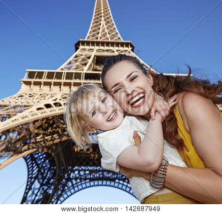 Smiling Mother And Child Tourists Against Eiffel Tower In Paris