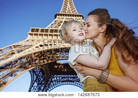 Happy Mother And Child Tourists Kissing Against Eiffel Tower