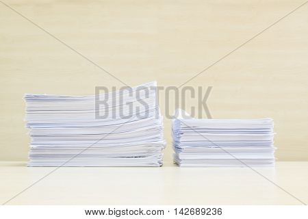 Closeup pile of work paper on blurred wooden desk and wall textured background in the meeting room under window light hard work concept with copy space