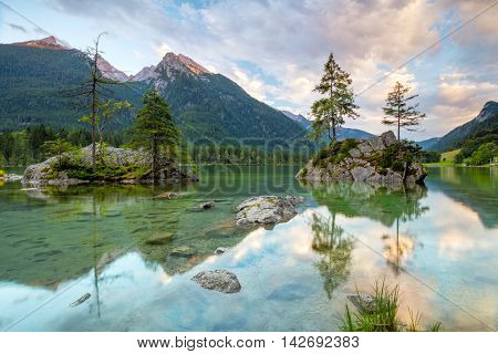 Beautiful scene of trees on a rock island and mountains at sunrise time in summer, Lake Hintersee National park Berchtesgadener Land, Upper Bavaria, Germany, Europe