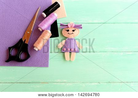 Handmade cute doll, scissors, thread, needle, felt sheets on wooden background with blank space for text. How simply and cheaply make a children toy. Creative doll crafts with felt for kids