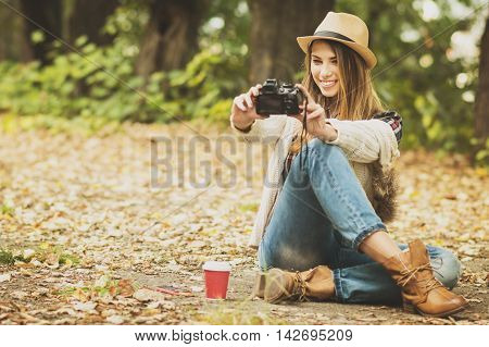 Young millennial blonde Caucasian woman taking a selfie on digital camera in park in autumn. Cool teenage girl photographing herself using digital camera. Matte filter, natural light.
