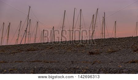 Sailing boat masts, showing behind a pebble beach, littered with flotsam and jetsam, at sunset, against a red sky