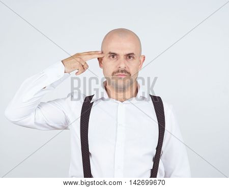Bald Crazy Mad Man In Wihte Shirt With A Finger To His Temple