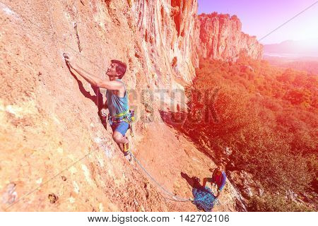 Team of Climbers Man and Woman ascending orange bright rocky Wall with rope and gear Male Leading Female belaying blue Sky and green Forest poster