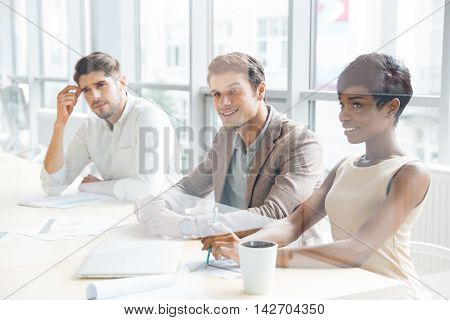 Smiling young business people sitting on training and making notes in office