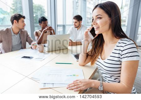 Happy successful young woman talking on cell phone on business meeting in conference room