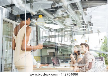 African american young businesswoman standing and making resentation in modern office