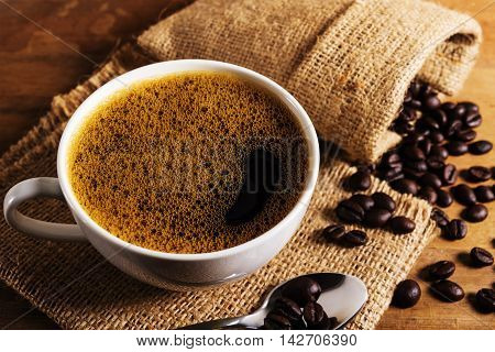 Coffee cup with coffee bean on brown wooden table in still life and filter color tone
