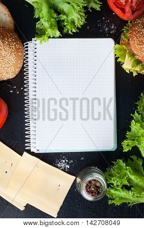 Hamburger with salad cheese tomato meat on black backdrop. Popular snack template.