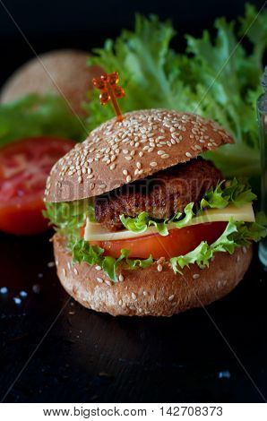 Hamburger with salad cheese tomato meat on black backdrop. Popular snack.