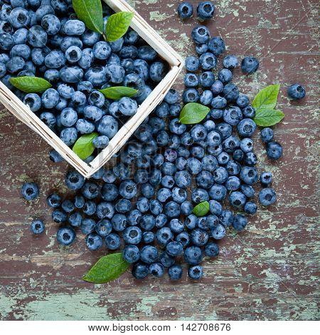 Freshly picked juicy blueberries in basket on wooden background