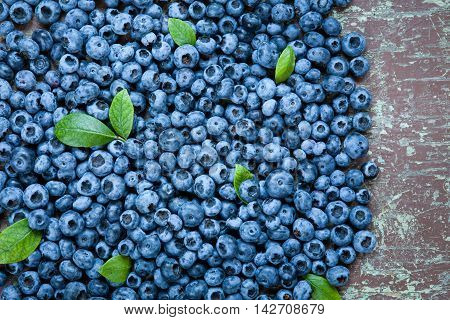 Ripe blueberries with green leaves on wooden table close up