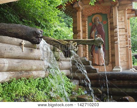 Water flow from the spring through the channels of tree trunks on the background of the chapel.