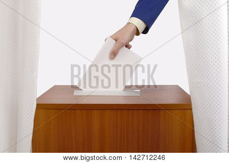 man's hand casts a ballot in the ballot box at the polling station