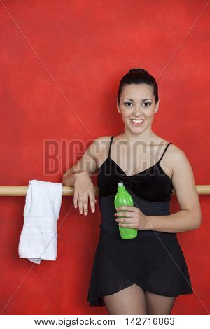 Ballerina Smiling While Holding Water Bottle In Training Studio