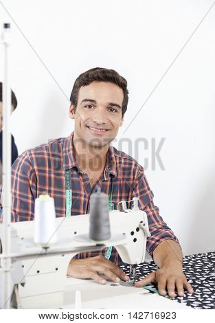 Smiling Tailor Sitting At Workbench In Factory