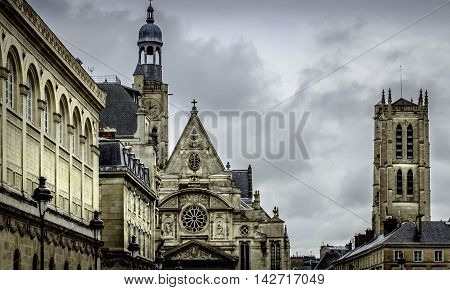 Church steeples in Paris, France against dark rain clouds