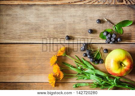Calendula flowers, aronia berries (black chokeberry) and apple on wooden background in rustic style. Top view.