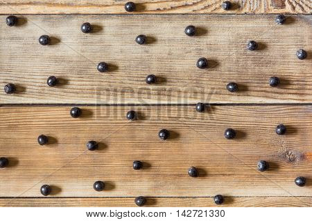 Aronia berries (black chokeberry) on wooden background in rustic style. Top view.