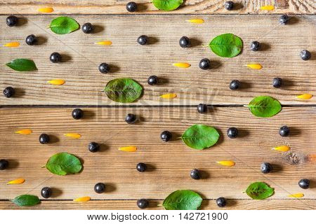 Aronia berries (black chokeberry) calendula petals and leaves on wooden background in rustic style. Top view.