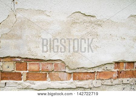 Broken vintage bricklaying wall fragment from old red clay bricks and damaged plaster background texture