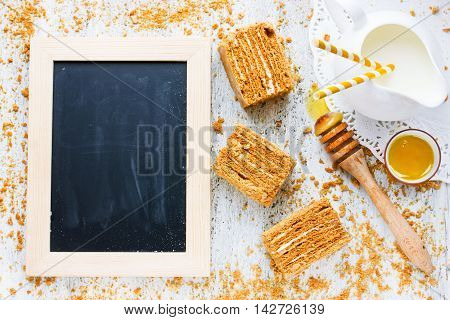 Honey cake pieces honey milk and crumbs on white wooden table top view blank space for text on the chalkboard