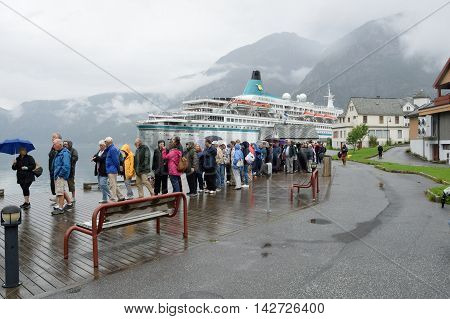 Eidfjord Norway - July 29 2016: Large group of tourists from cruise ship on tour during rainy day