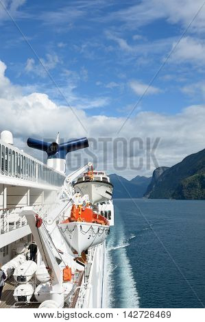 Geirangerfjord Norway - July 31 2016: View of Geirangerfjord Norway from rear of cruise ship Magellan with lifeboats and funnel
