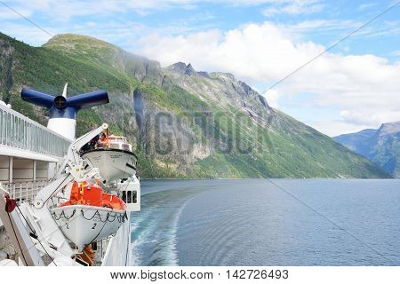 Geirangerfjord Norway - July 31 2016: View of Geirangerfjord Norway from rear of cruise ship turning with fjord in background