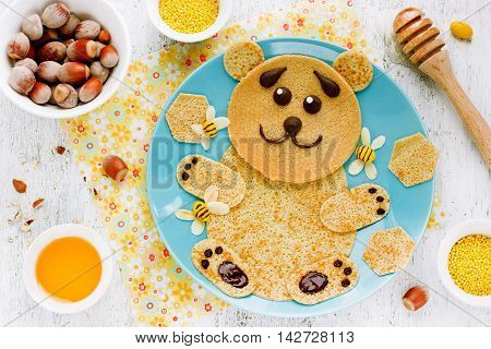Bear-shaped pancakes with honey and nuts - creative idea for children breakfast funny food art for kids edible picture on plate top view