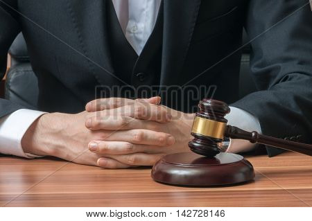 Law and justice concept. Judge or magistrate has clapsed hands. Wooden gavel in front.