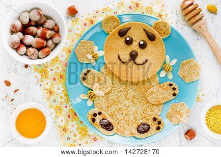Pancakes in the shape of cute bear with honey and nuts for kids breakfast funny food art idea for children top view