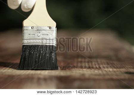 Paintbrush sliding over wooden surface protecting wood for exterior influences weathering insects and fungus. Carpentry woodwork home improvement do-it-yourself concept with copy space.