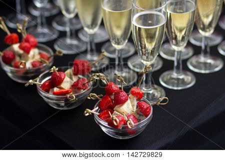 Canapes of cheese and strawberries in vases in the background are glasses of champagne