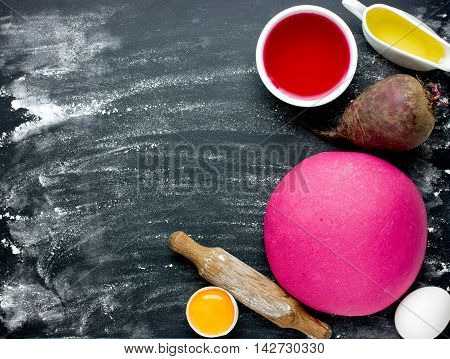 Pink beet dough and ingredients on a black background. Making beetroot pasta on a black background with flour blank space for text top view