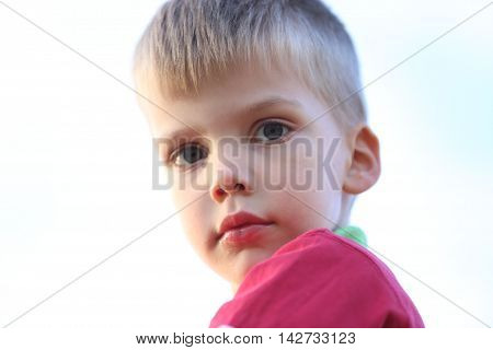 close up of a little boy playing outside with white sky behind him