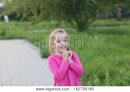 little girl wearing pink shirt lauging and playing at a playground
