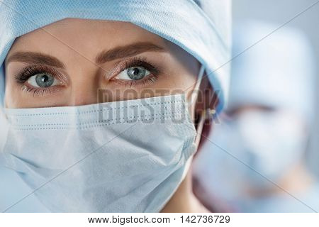 Close up portrait of female surgeon doctor wearing protective mask and cap. Healthcare medical education emergency medical service and surgery concept