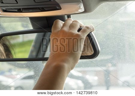 in the car the girl adjusts the rear view mirror