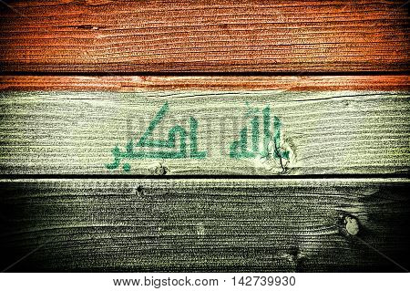flag of Iraq painted on old grungy wooden background