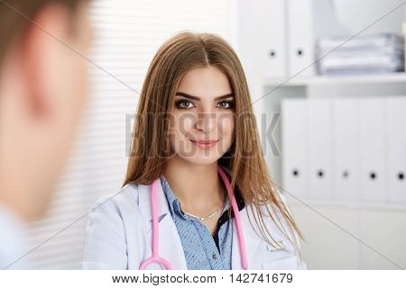Beautiful smiling female doctor portrait in office with male visitor. Physical exam er disease prevention ward round 911 therapeutist prescribe remedy healthy lifestyle concept