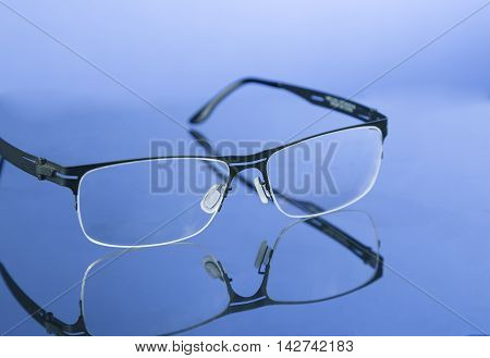 Reading moden eyeglasses on nice blue background with reflection.