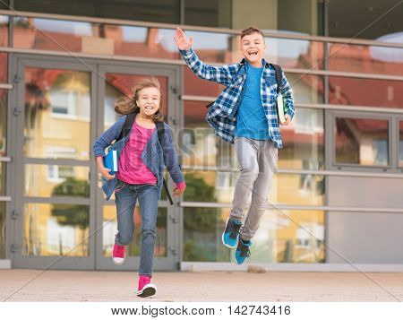 Happy children - boy and girl with books and backpacks on the first school day. Excited to be back to school after vacation. Full length outdoor portrait.