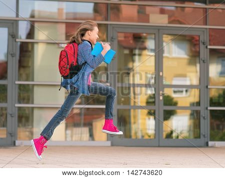 Happy girl with book and backpack on the first school day. Excited to be back to school after vacation. Full length outdoor portrait.