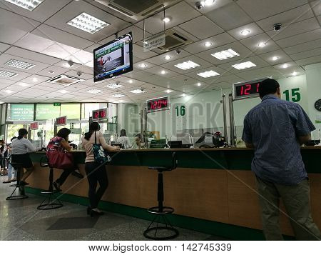 Hanoi, Vietnam - Aug 15, 2016: Customer making banking transactions at the counter of Joint Stock Commercial Bank for Foreign Trade of Vietnam (VCB). VCB is one of the biggest bank in Vietnam.