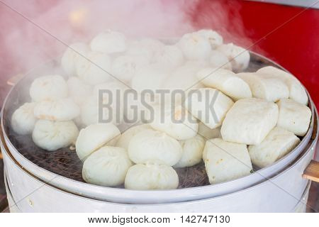 Big steamer with differently sized Chinese mantou and baozi a filled bread specialty from China