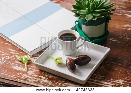 Hipster easter. Flat lay photography: cup of coffee, chocolate egg, old magazine, succulent cactus and vintage napkin in a rustic wood table.
