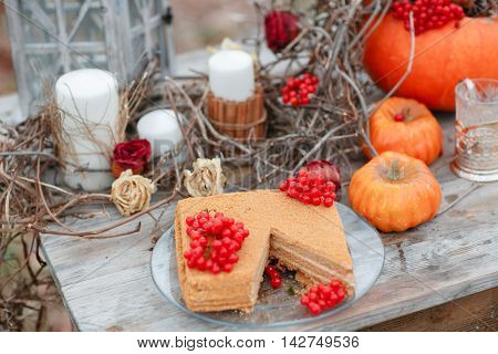 halloween inspiration. Autumn still life. pumpkin, dry roses, viburnum honey cake. Honey in a vase. dry twigs. on the table
