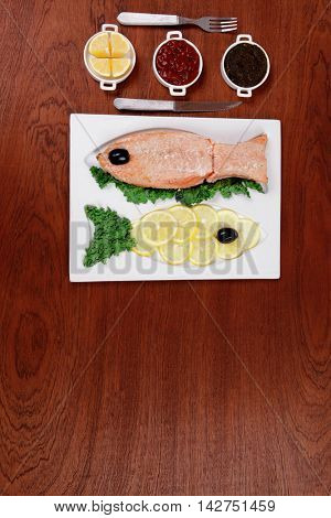 healthy food fresh roast red fish salmon with kale lemon antipasto ketchup sauce on white plate over wooden table